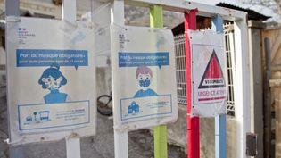 Des messages informatifs sur la grille d'une école de Briançon (Hautes-Alpes), le 16 février 2021. (THIBAUT DURAND / HANS LUCAS / AFP)