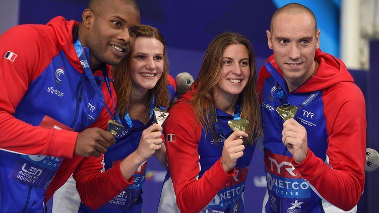 Jeremy Stravius, Mehdy Metella, Marie Wattel et Charlotte Bonnetposent après leur médaille d'or en relais mixte 4X100 nage libre, aux championnats d'Europe de natation, le 8 août 2018. (OLI SCARFF / AFP)