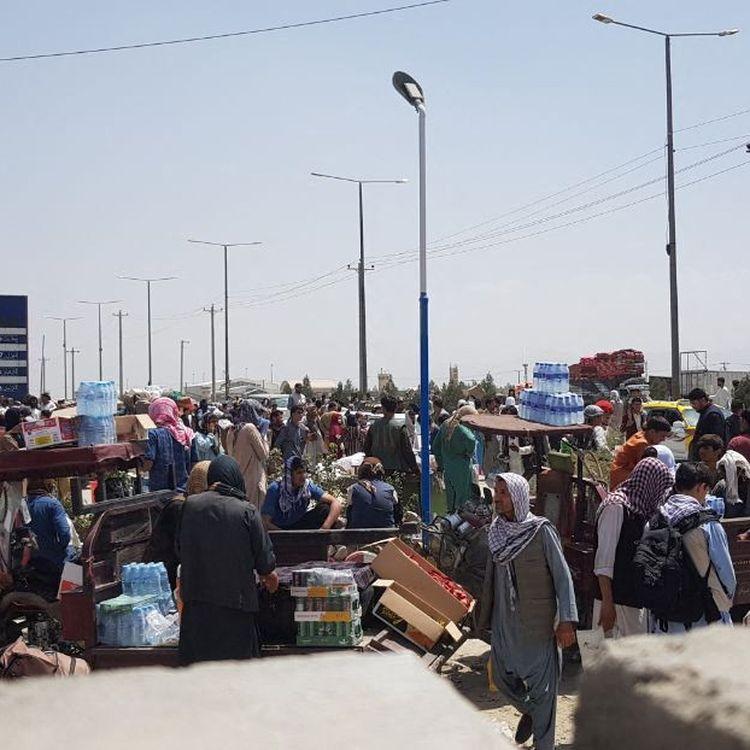 Des dizaines d'Afghans patientent aux abords de l'aéroport de Kaboul (Afghanistan),dans l'espoir d'être évacués, le 21 août 2021. (SAYED KHODAIBERDI SADAT / ANADOLU AGENCY / AFP)