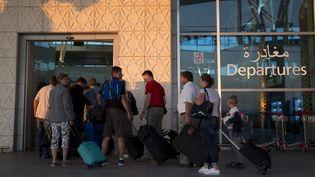 Des touristes s'apprêtent à embarquer à l'aéroport d'Enfidha, pour quitter la Tunisie. (KENZO TRIBOUILLARD / AFP)