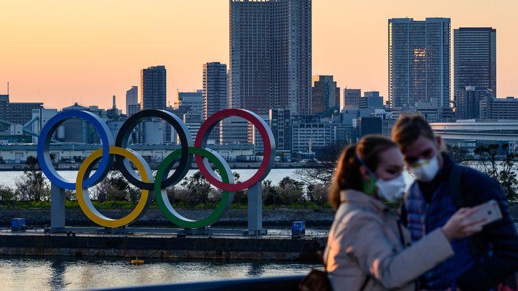 Des personnes portant des masques se prennent en photo devant les anneaux olympiques à Tokyo, au Japon, le 6 mars 2020. (PHILIP FONG / AFP)