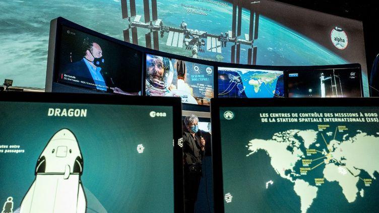"""Des écrans montrent l'avancée de la capsule """"Crew Dragon"""", à la Cité de l'espace, à Toulouse (Haute-Garonne), après le décollage de Thomas Pesquet et de trois autres astronautes, le 23 avril 2021. (FREDERIC SCHEIBER / HANS LUCAS / AFP)"""