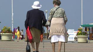 Deux personnes âgées marchent le long de la plage à Deauville (Calvados), le 30 août 2000. (MYCHELE DANIAU / AFP)
