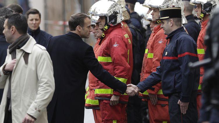 """Emmanuel Macron serrant la main d'un pompier, après la mobilisation des """"gilets jaunes"""", à Paris, le 2 décembre 2018. (GEOFFROY VAN DER HASSELT / AFP)"""