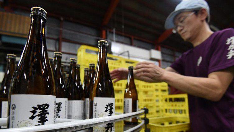 Dans la brasserie Ozawa Shuzo située à Ome, à l'ouest de Tokyo, des centaines de bouteilles s'apprêtent à être livrés aux quatre coins du Japon et du monde. (TORU YAMANAKA / AFP)