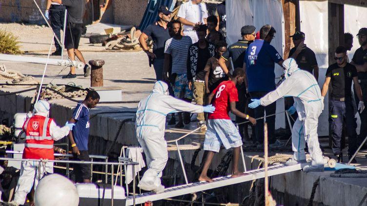 """L'un des27 mineurs non-accompagnés arrive sur l'île italienne de Lampedusa après avoir été évacué du navire de sauvetage de l'ONG espagnole """"Open Arms"""", amarré au large des côtes de l'île, le 17 août 2019. (ALESSANDRO SERRANO / AFP)"""