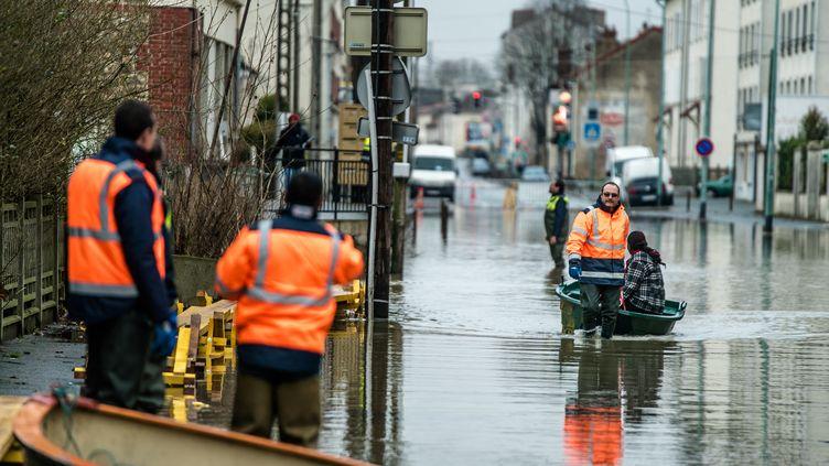 Des employés municipaux aident les habitants de Villeneuve-Saint-Georges (Val-de-Marne), après les crues de la Seine et de l'Yerres, le 26 janvier 2018. (SIMON GUILLEMIN / HANS LUCAS / AFP)