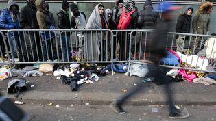 Des réfugiés font la queue devant un centre d'acceuil de réfugiés, à Paris, en janvier 2017. (GEOFFROY VAN DER HASSELT / AFP)