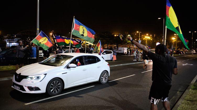Des indépendantistes arborent le drapeau kanakau soir du deuxième référendum sur l'indépendance de la Nouvelle-Caldéonie, le 4 octobre2020, àNouméa. (THEO ROUBY / AFP)