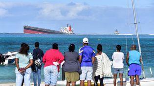 """Des habitants observent le naufrage du """"MVWakashio"""", le 6 août 2020, dans le sud-est de l'île Maurice. (DEV RAMKHELAWON / L'EXPRESS MAURICE / AFP)"""