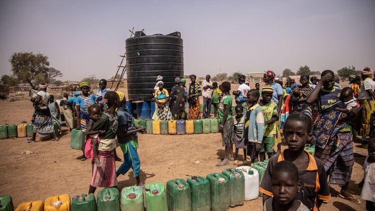 Des réfugiés font la queue pour avoir de l'eau dans un camp à Barsalogho, au Burkina Faso, le 27 janvier 2020. (OLYMPIA DE MAISMONT / AFP)