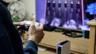Un joueur teste la nouvelle PlayStation 5 dans son salon. Photo d'illustration.  (YELIM LEE / AFP)