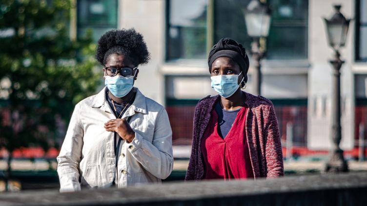 Des passantes portent un masque sanitaire à Paris, le 15 mai 2020. (LUDIVINE PELLISSIER / HANS LUCAS / AFP)