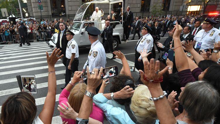 Des personnes prennent des photos du pape François dans sa papamobile, le 24 septembre 2015, à New York. (TIMOTHY A. CLARY / AFP)