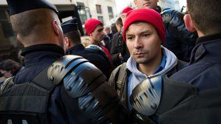 David van Hemelryck encadré par des policiers après que des militants portant des bonnets rouges ont hué le président de la République, à Paris, le 11 novembre 2013. (LCHAM / SIPA)