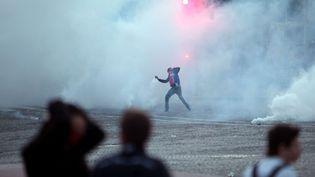 Un supporter du PSG jette des gaz lacrymogènes place du Trocadéro à Paris, le 13 mai 2013. (THIBAULT CAMUS / AP / SIPA )