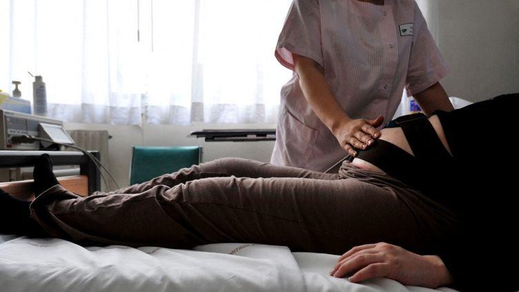 Une sage-femme rend visite à une femme enceinte à la maternité à Caen, le 17 février 2009. (MYCHELE DANIAU / AFP)