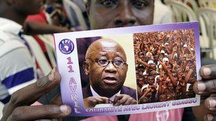 Un partisan de Laurent Gbagbo brandit un tract à l'effigie de l'ancien président ivoirien, où l'on peut lire «11 avril - Solidarité avec Laurent Gbagbo», pendant une manifestation le 11 avril 2015 marquant l'anniversaire de son l'arrestation    (AFP PHOTO/SIA KAMBOU)