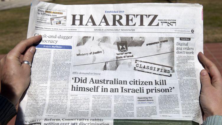 """Une femme lit le quotidien israélien """"Haaretz"""", qui évoque le suicide d'un prisonnier australien, présenté comme un agent du Mossad, dans des circonstances étranges, le 13 février 2013, à Jérusalem. (AHMAD GHARABLI / AFP)"""