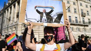 """Un manifestant tient une pancarte avec une photo du Premier ministre hongrois Viktor Orbán, lors d'un rassemblement à Budapest (Hongrie) contre la loi interdisant la """"promotion"""" de l'homosexualité le 14 juin 2021. (GERGELY BESENYEI / AFP)"""