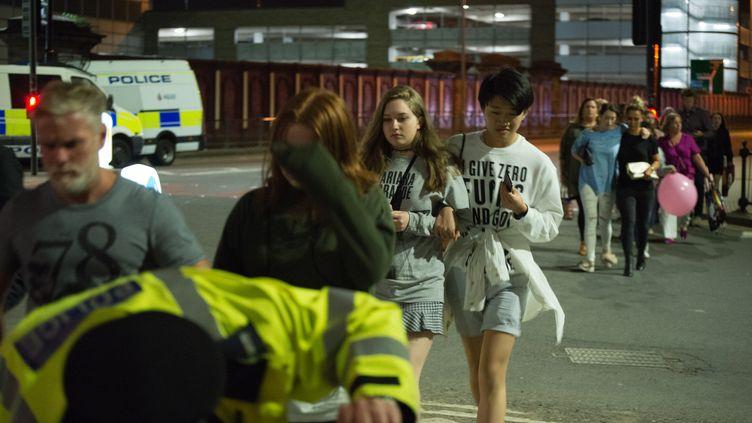 Les spectateurs quittent la Manchester Arena, où se tenait un concert de la chanteuse américaine Ariana Grande, le 22 mai 2017 à Manchester (Royaume-Uni). (JONATHAN NICHOLSON / NURPHOTO / AFP)