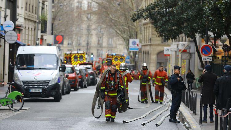 Des pompiers et un policier, dans la rue Erlanger, dans le 16e arrrondissement de Paris, où un violent incendie a fait au moins 10 morts, dans la nuit du 4 au 5 février 2019. (PHOTOPQR / LE PARISIEN / MAXPPP)
