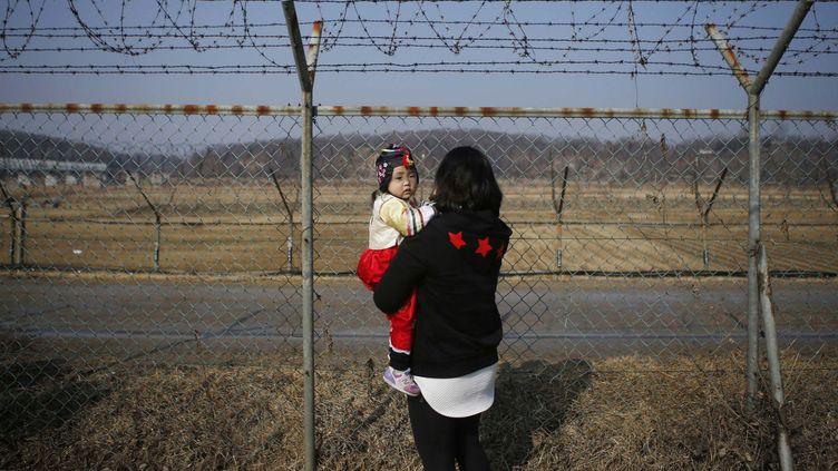 Une femme tient sa fille dans ses bras à la frontière entre la Corée du sud et la Corée du nord (KIM HONG-JI / REUTERS)