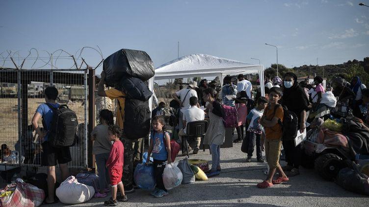Des migrants font la queue pour entrer dans un nouveau camp pour les demandeurs d'asile, le 12 septembre 2020, près de Panagiouda, sur l'île grecque de Lesbos. (LOUISA GOULIAMAKI / AFP)