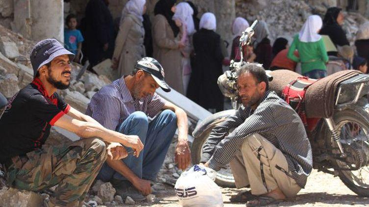 Des habitants de Daraya, une des villes symbole du soulèvement syrien, le 28 mai 2016 aux pieds d'immeubles dévastés par les barils d'explosifs largués par les avions du régime. (FADI DIRANI/AFP)