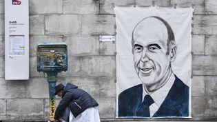 L'artiste Perez Roge, dit Rog, accroche un portrait de Valéry Giscard d'Estaing, le 9 décembre 2020, à Paris. (STEPHANE DE SAKUTIN / AFP)