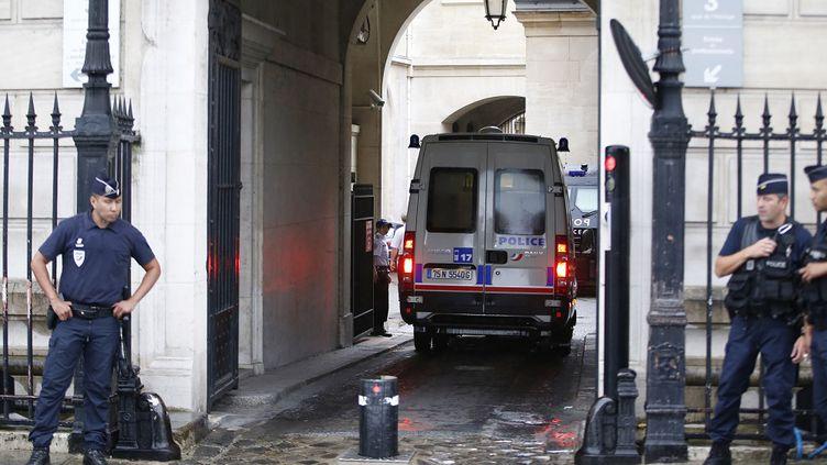Un car de police arrive au 36, quai des Orfèvres, à Paris, après la garde à vue d'un officier de la brigade des stupéfiants soupçonné d'avoir pris part au vol de 52 kilos de cocaïne, le 6 août 2014. (KENZO TRIBOUILLARD / AFP)