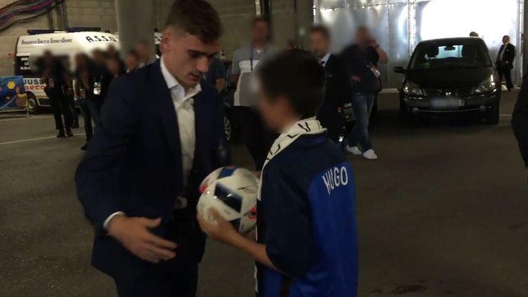 L'attaquant de l'équipe de France, Antoine Griezmann, remet le ballon du match France-Irlande, le 26 juin au Parc OL, au fils du policier assassiné à Magnanville. (POLICE NATIONALE / TWITTER)