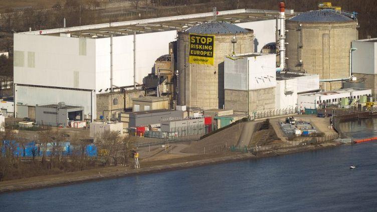 Une banderolle hostile au nucléaire est déployée par des militants Greenpeace sur un des réacteurs de la centrale de Fessenheim (Haut-Rhin), le 18 mars 2014. (SEBASTIEN BOZON / AFP)