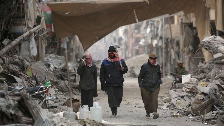 Des Syriens au milieu des décombres dans la ville de Raqqa en Syrie, le 11 janvier 2018. (DELIL SOULEIMAN / AFP)
