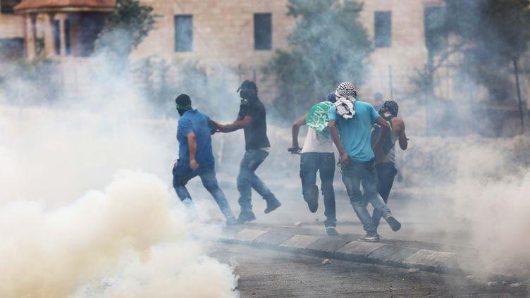Des Palestiniens visés par des tirs de gaz lacrymogènes, le 23 octobre 2015, àBethléem. (MUHESEN AMREN / NURPHOTO / AFP)