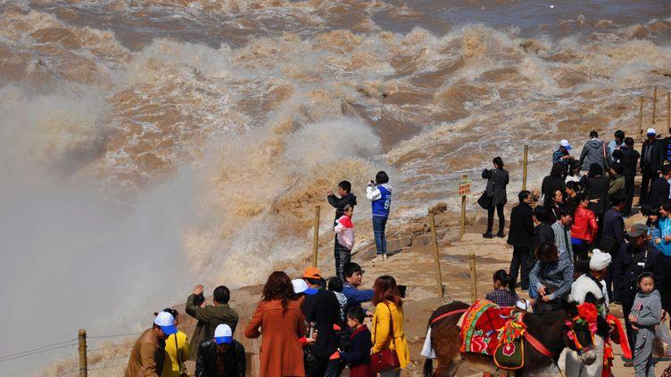 Des Chinois se rassemblent pour regarder le Hukou, des chutes sur lefleuve Jaune dans laprovince du Shanxi, au nord de la Chine, le 22 Mars 2014. (CHINE NOUVELLE / SIPA)