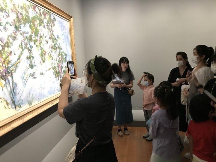 Une enseignante initie ses élèves à la peinture impressionniste lors de l'exposition à Shanghai, juillet 2021 (DOMINIQUE ANDRÉ / RADIO FRANCE)