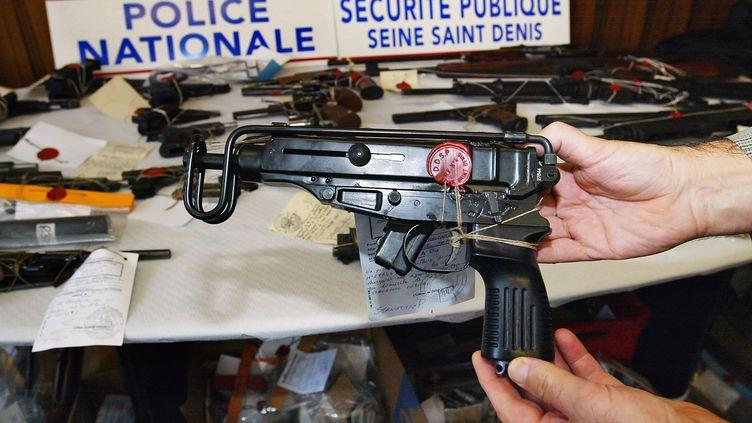 Un policier présente, le 11 septembre 2003, un pistolet mitrailleur Scorpio saisi à Montreuil, en Seine-Saint-Denis. (JACK GUEZ / AFP)