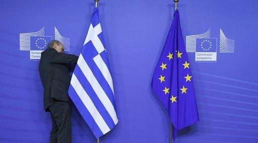 Les drapeaux grec (à gauche) et européen (à droite) à Bruxelles le 4 février 2015. L'homme qui ajuste le drapeau grec, juste avant la visite du Premier ministre grec Alexis Tsipras, semble avoir du mal... De méchantes langues pourraient y voir un symbole des difficultés de la Grèce au sein de l'UE... (AFP - Yves Herman)