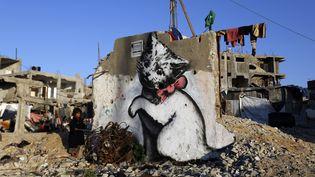 Un chaton peint sur un pan de mur, parmi les ruines de Gaza, près d'un enfant. Un moyen comme un autre d'attirer l'attention du monde sur une enclave dévastée par la guerre.  (Mohammed Abed / AFP)
