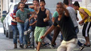 Des Palestiniens transportent l'un des leurs, blessés dans un accrochage avec l'armée israélienne, le 4 octobre 2015 à Jenin (Cisjordanie). (ABED OMAR QUSINI / REUTERS)