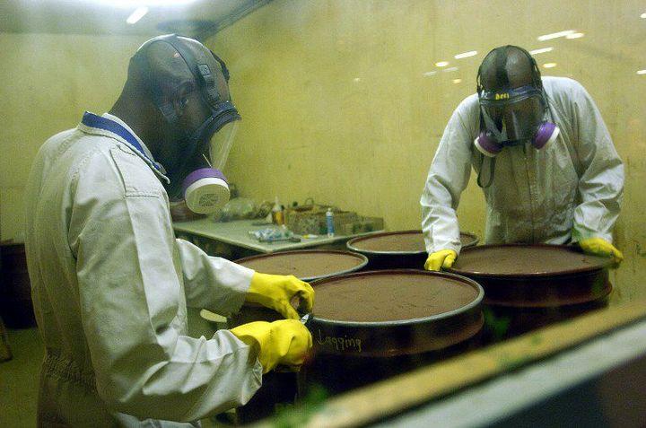 Des travailleurs sud africains vérifient des fûts contenant des déchets nucléaires avant de les stocker. (Photo AFP/Guercia Gianluigi)