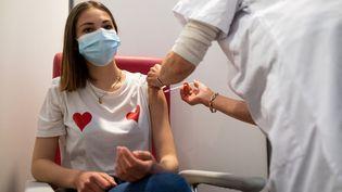 Une jeune femme reçoit une dose de vaccin contre le Covid-19 à Dinan (Côtes-d'Armor), le 30 avril 2021. (MARTIN BERTRAND / HANS LUCAS / AFP)