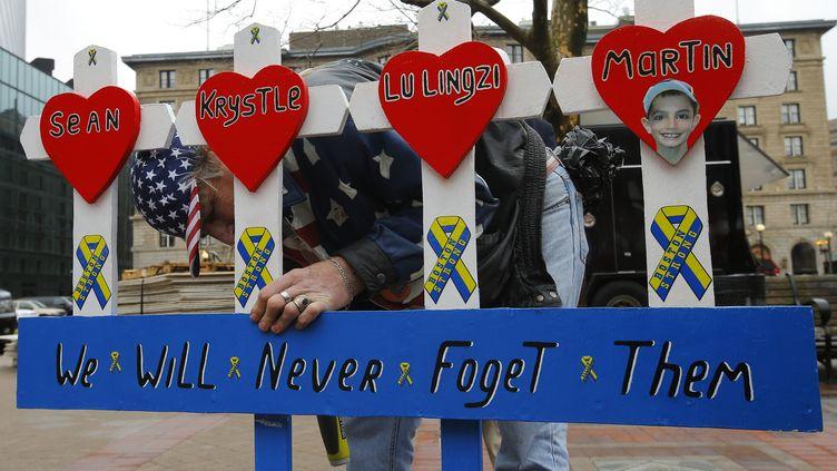Un homme installe un mémorial pour les victimes des attentats du marathon de Boston, le 15 avril 2014. ( BRIAN SNYDER / REUTERS )