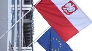 Le drapeau polonais et celui de l'Union européen, le 8 octobre 2021 à l'entrée de l'ambassade de Pologne à Bruxelles (Belgique). (KENZO TRIBOUILLARD / AFP)