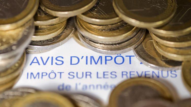 Avis d'imposition à peine caché par des pièces de monnaie. (JOEL SAGET / AFP)