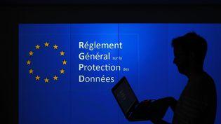 Un homme présente avec son ordinateur portable le RGPD en projection. (MAXPPP)