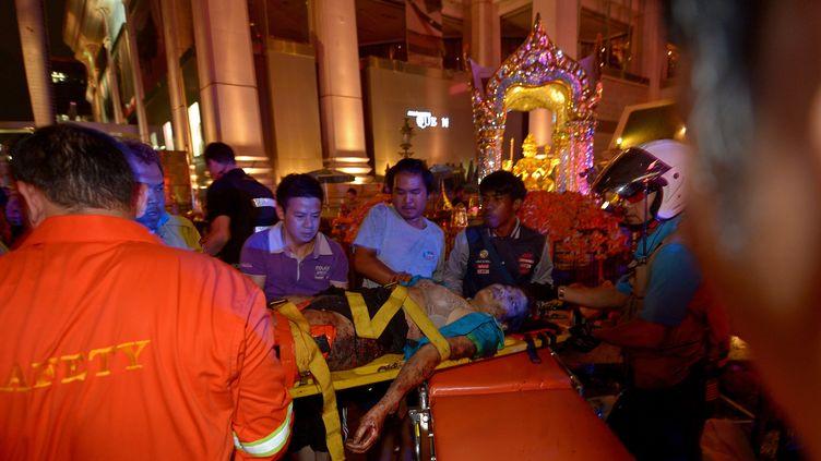 Les équipes de sauveteurs transportent un des blessés après l'explosion d'une bombe au centre de Bangkok le 17 août 2015. (PORNCHAI KITTIWONGSAKUL / AFP)