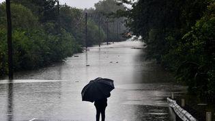 Un homme face à une route inondée dans la banlieue de Richmond (Australie), le 22 mars 2021. (SAEED KHAN / AFP)