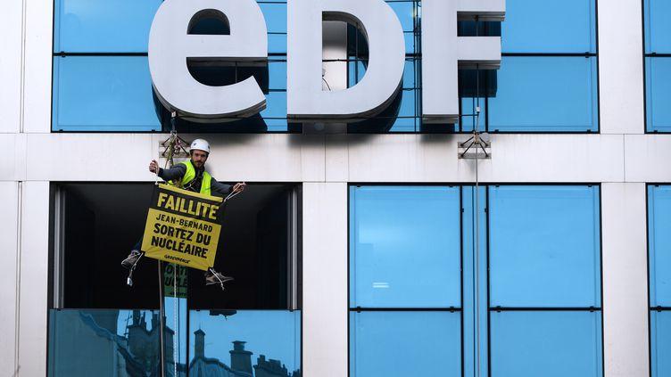 Un militant Greenpeace durant une action au siège d'EDF, le 14 février 2017. (ERIC PIERMONT / AFP)